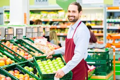 Hypermarket clerk filling up storage racks